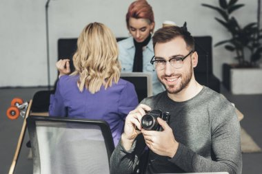 selective focus of smiling photographer looking at camera with colleagues behind in office