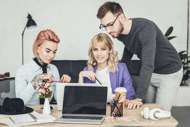 portrait of group of creative workers discussing new idea at workplace in office