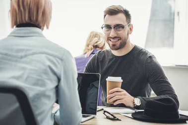 selective focus of smiling businessman in eyeglasses with coffee to go at workplace in office