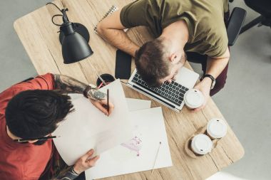 Overhead view of designer and sleeping coworker at table together in office