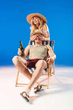 Smiling woman covering face of man holding beer while sitting in deck chair on blue background