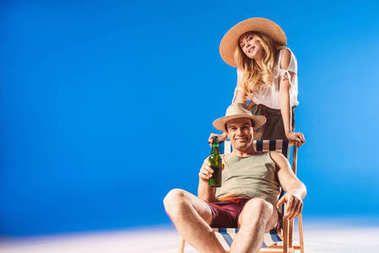 Blonde woman leaning on chair with man in straw hat holding beer on blue background