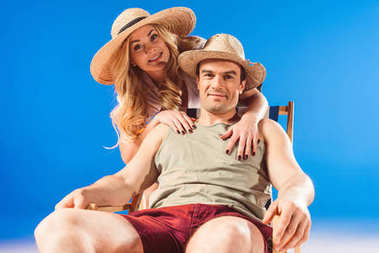Woman embracing man resting in deck chair isolated on blue