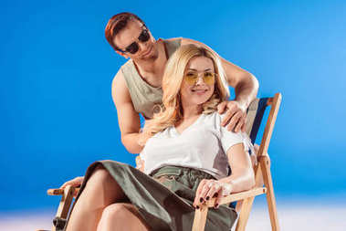 Man hugging woman sitting in deck chair on blue background
