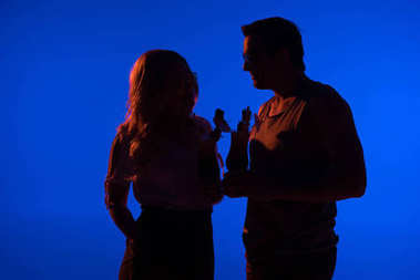 Silhouette of beautiful woman and man holding cocktails isolated on blue in dark light