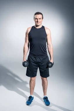 Active man exercising with dumbbells on grey background