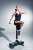 Fiatal nő lépés a szürke háttér platform jumping