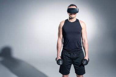 Young man athlete lifting dumbbells while wearing vr glasses on grey background