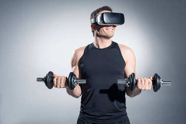 Active man training with dumbbells while wearing vr glasses on grey background