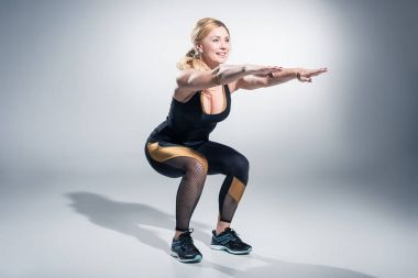 Smiling woman athlete performing squats on grey background