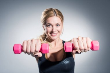 Young woman exercising with dumbbells on grey background