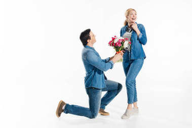 Man standing on one knee and giving happy woman a bouquet of flowers isolated on white