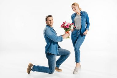 Boyfriend standing on one knee and giving blonde woman a bouquet of flowers isolated on white