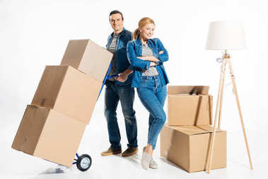 Couple moving cardboard boxes on hand cart isolated on white
