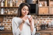 Fotografie glücklich attraktive afrikanische amerikanische Frau, die Tasse Kaffee in der Küche