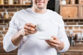 cropped shot of smiling man holding white cup of coffee and saucer