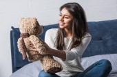 Photo beautiful smiling african american girl holding teddy bear while sitting on bed