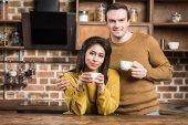 boldog többnemzetiségű pár kávét iszik, és mosolyogva kamera konyhában