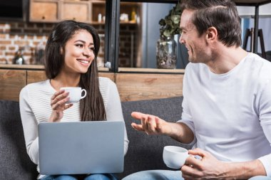 multiethnic couple smiling each other and talking while drinking coffee and using laptop at home