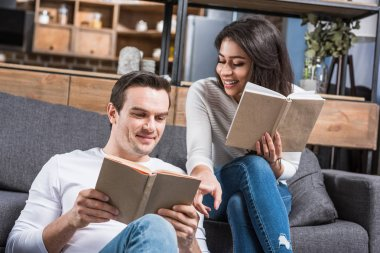 happy multiethnic couple reading books together at home