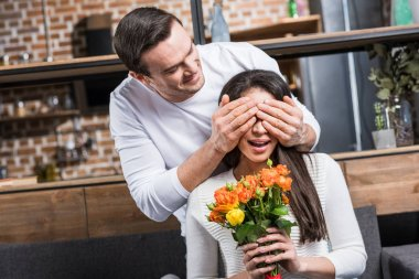 happy man closing eyes to girlfriend holding bouquet of flowers at home