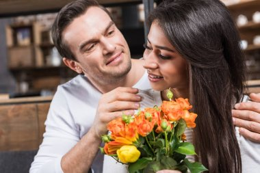 smiling man embracing girlfriend holding bouquet of flowers at home