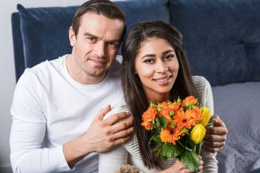 happy young man embracing girlfriend with bouquet of flowers and smiling at camera