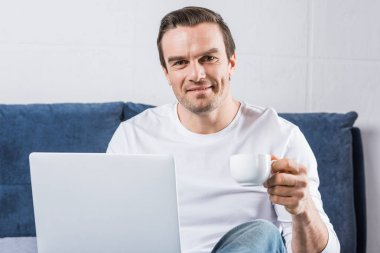 Man holding cup of coffee and smiling at camera while using laptop on bed stock vector