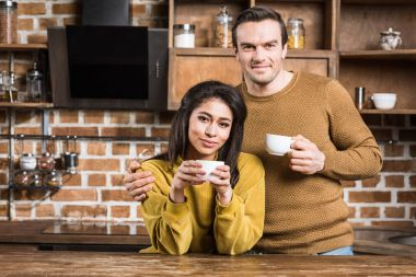 happy multiethnic couple drinking coffee and smiling at camera in kitchen