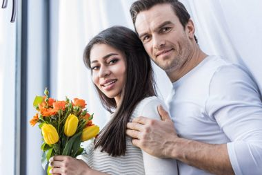 happy multiethnic couple embracing and smiling at camera while woman holding beautiful flower bouquet