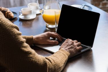 cropped shot of man using laptop with blank screen during breakfast