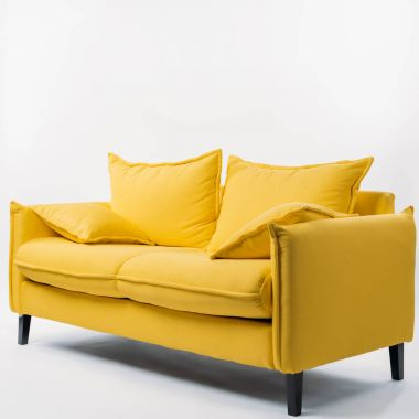 studio shot of yellow couch with pillows, on white