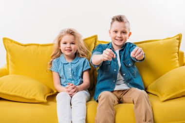 little driver sitting on yellow sofa with sister