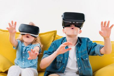 excited siblings using virtual reality headset and sitting on yellow sofa