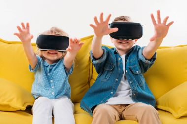 siblings gesturing and using virtual reality headset while sitting on sofa