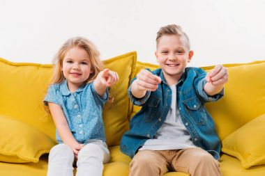 little boy driving and sister pointing while sitting on yellow sofa