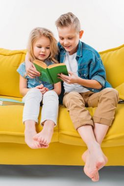 siblings reading book and sitting on yellow sofa