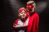 átölelve a szuperhős-jelmezek és piros maszkok testvérek