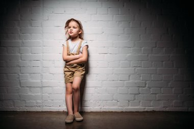 child in safari costume with crossed arms standing at white wall