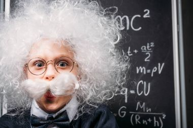 little Einstein in eyeglasses with theory of relativity on chalkboard