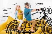 Boy předstírá biker a motocykl na koni v sedle na žluté pohovce se sestrou