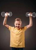 Fotografia sorridente ragazzo che finge di essere un sportsman e formazione con i manubri, isolata su grey