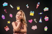 Photo adorable thoughtful child in pink dress, isolated on grey with birthday icons