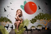 Fotografie female child in safari costume and hat sitting at white wall with safari animals illustration