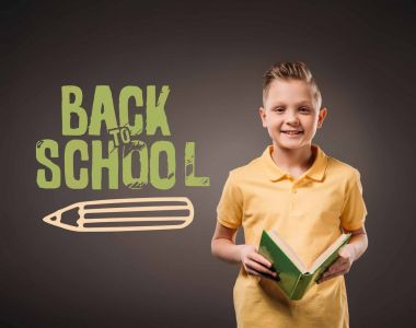 preteen smiling boy holding book, isolated on grey with back to school lettering and pencil illustration