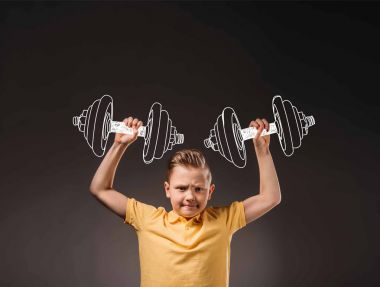 preteen boy pretending to be a sportsman and lifting big drawn dumbbells, isolated on grey