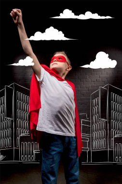 boy flying in superhero costume and red mask in city