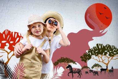 siblings in safari costumes hugging and looking in binoculars at zebra, elephants and antelopes