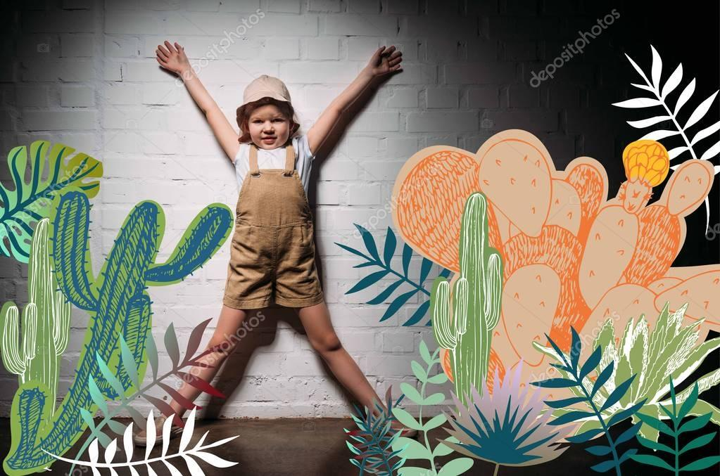 Little child in safari costume standing at white wall with cactuses illustration