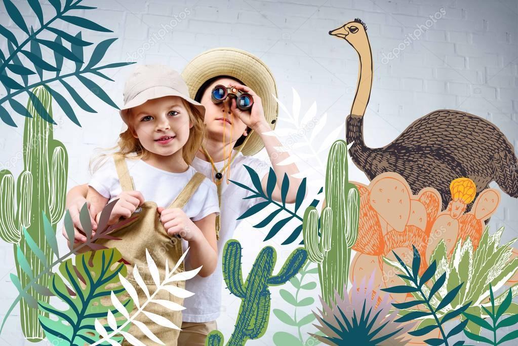 Siblings in safari costumes hugging and looking in binoculars at cactuses and ostrich